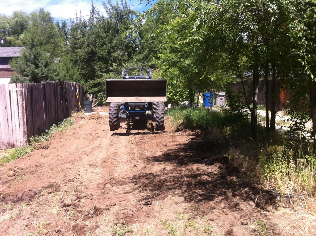 Dad starts his tractor to leve out the parking spot