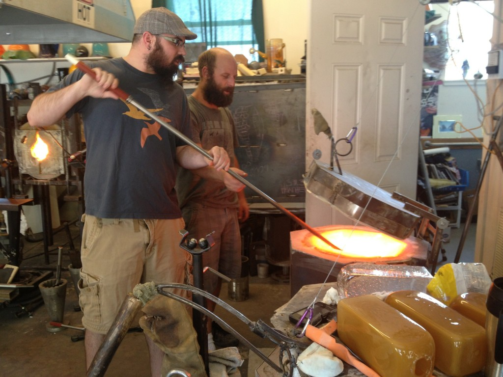 My brother Dan is brave enough to volunteer first, or rather be volunteered first! :) Here he is taking the metal tube (I don't know the names of these tools so I am just going to describe them :) ) and dipping it in the vault of melted glass, the temp inside this kiln is between 2100 and 2200 degrees, just a couple hundred degrees hotter than lava!