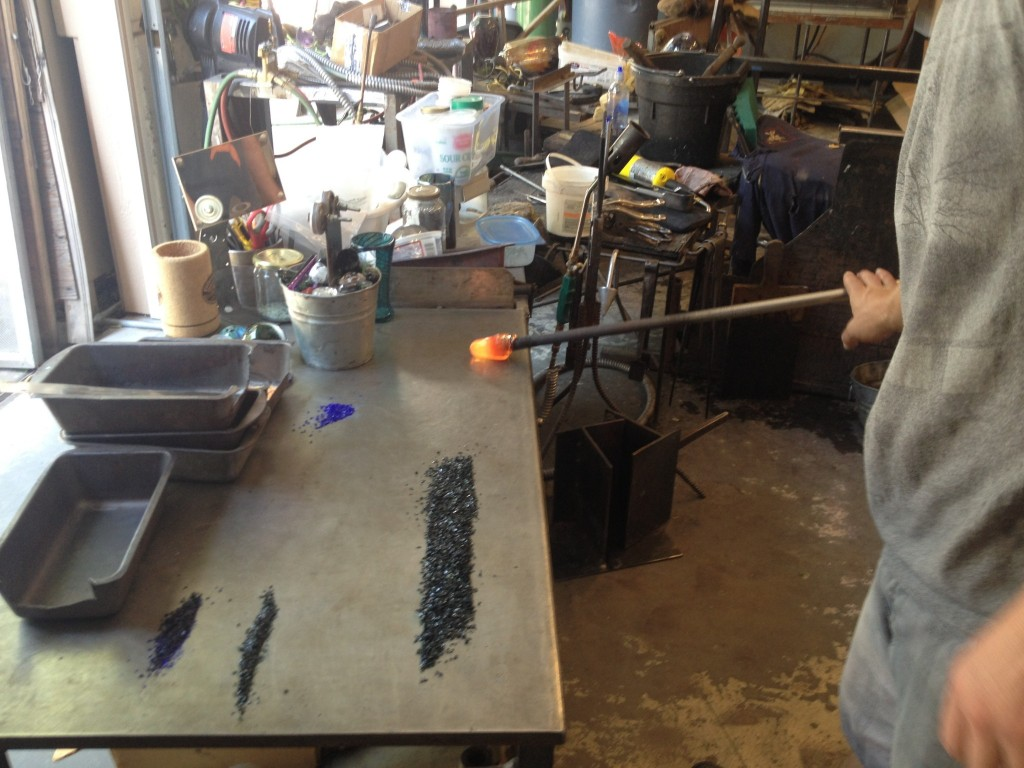 He chose to make a swirly emerald green sconce that has two spiral pieces of clear glass running down the sides. Here he is collecting the glass by rolling it in the steel table. the point of this small gather is to get the piece started, you roll it on the table to push the glass down sort of off the pipe.