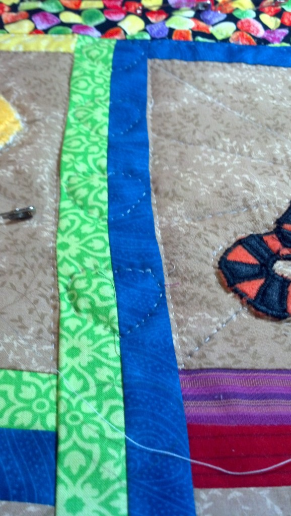 The pieces between the blocks are rainbow colors with little hearts quilted in